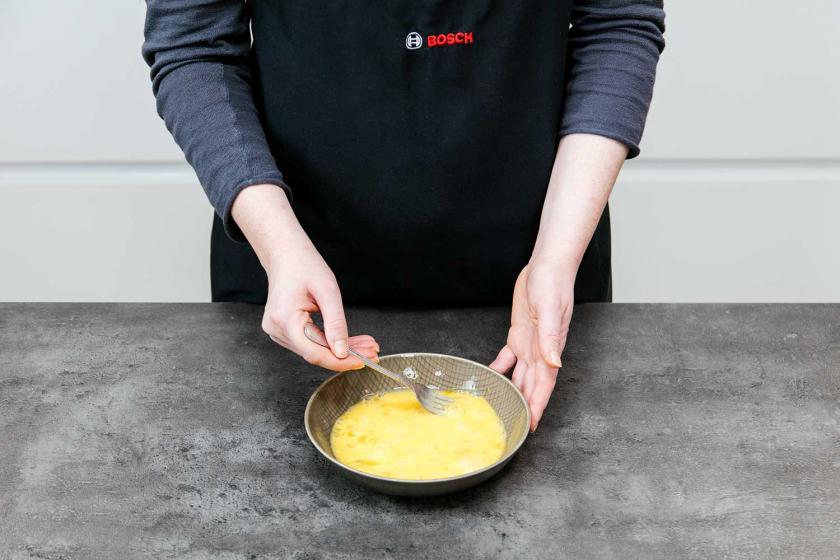 Für die Panade der Arancinis werden Eier verquirlt.
