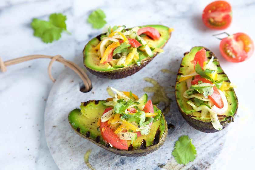Drei gefüllte Hälften von Avocado grillen liegen auf einem Brett.