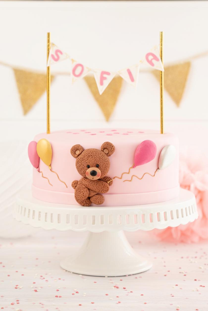 Rosafarbene Babyshower-Torte mit Wimpelkette auf weisser Tortenplatte.