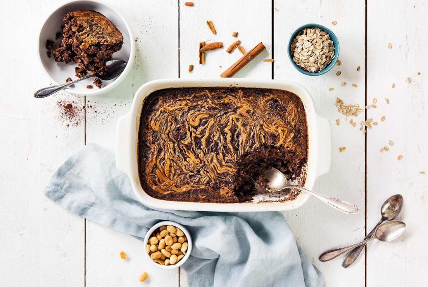 Baked Oatmeal auf einem Tisch. Drumherum Nüsse, Haferflocken.