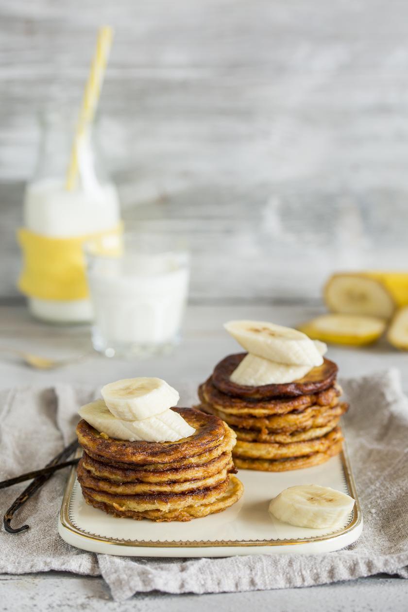 Mehrere Bananen Pancakes sind zu zwei Türmchen gestapelt und mit Bananenscheiben garniert.