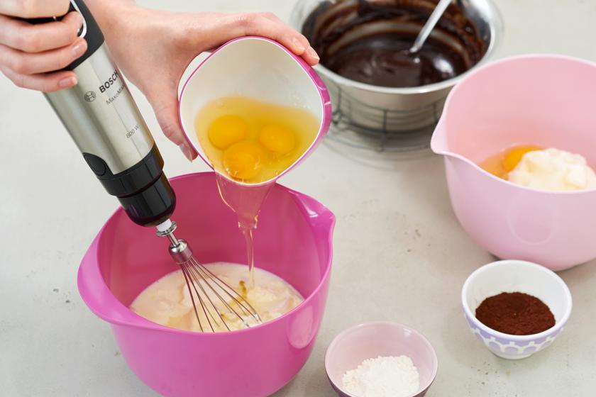 Für den Black and White Cheesecake werden Eier in die Rührschüssel mit Frischkäse gegeben.