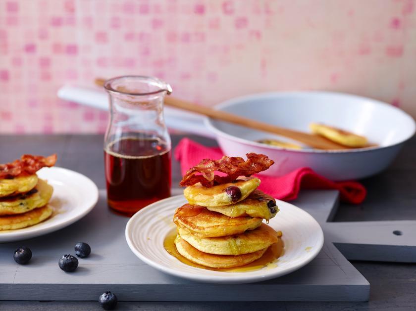 Mehrere Blaubeer-Pancakes auf einem Teller übereinander gestapelt.