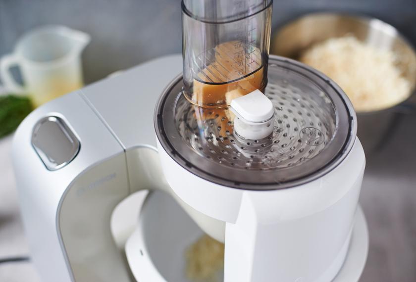 Parmesan für das Blumenkohl Risotto wird in einer Küchenmaschine gerieben.
