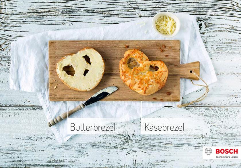 Butterbrezel und Käsebrezel nebeneinander auf einem Holzbrett.