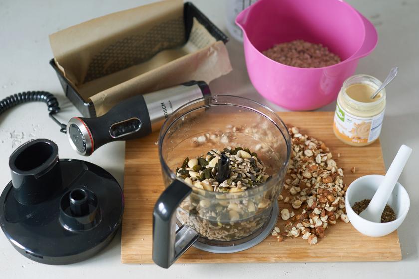 Kerne für das Brot ohne Mehl und weitere Zutaten und Schüsseln sind auf einem Tisch verteilt.