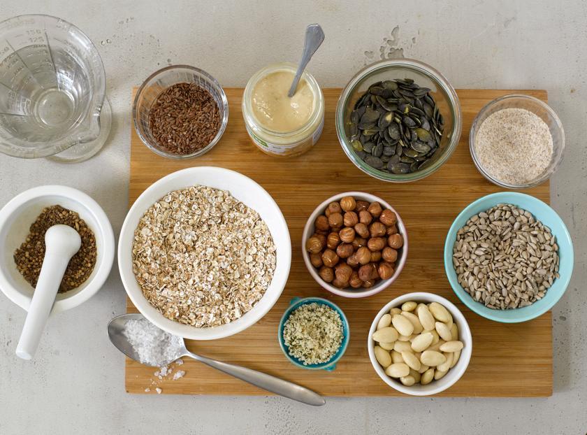 Zutaten für Brot ohne Mehl in Schüsseln auf einem Brett.