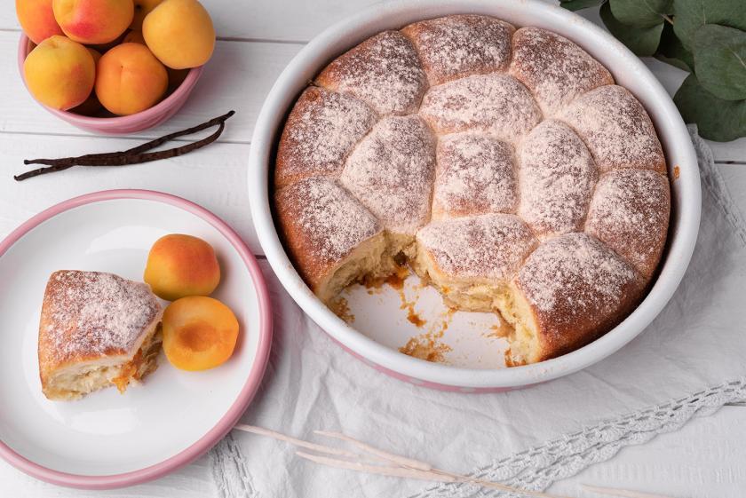 Buchteln mit Aprikosen-Mirabellen-Marmelade in einer Backform und auf einem Teller.