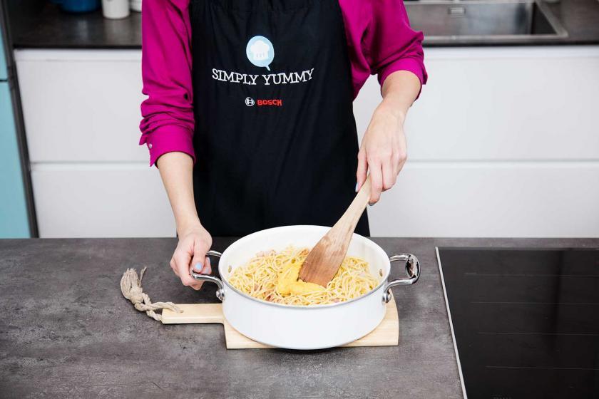 Für die Carbonara werden Spaghetti mit Ei-Käse-Mischung verrührt.