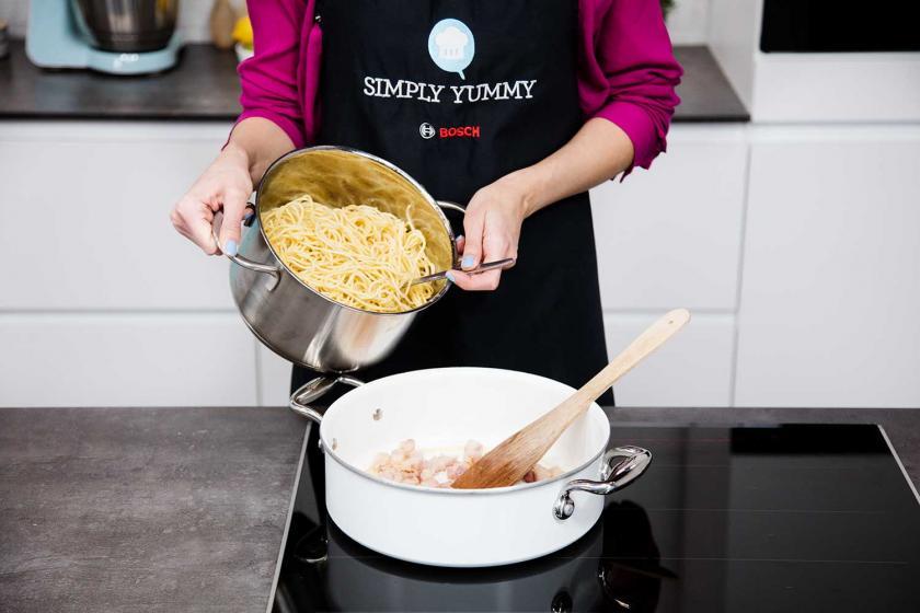 Spaghetti für die Carbonara werden in der Pfanne verrührt.