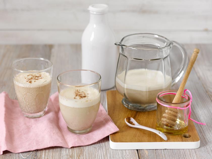 Chai-Smoothie in zwei Gläsern mit Karaffe und Honigglas