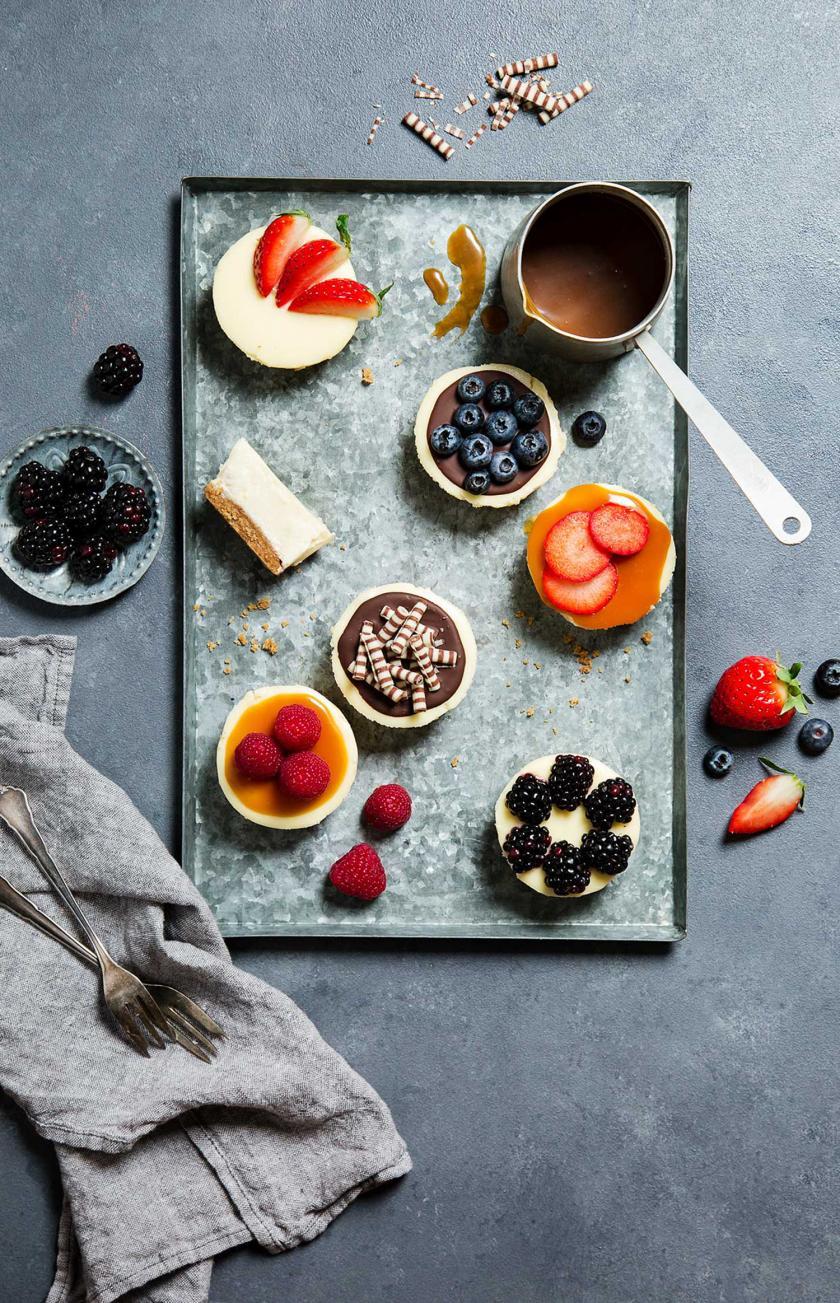Mehrere dekorierte Cheesecake-Muffins auf einem Backblech.