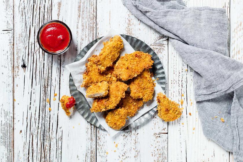 Chicken Nuggets auf einem Teller, daneben Ketchup.