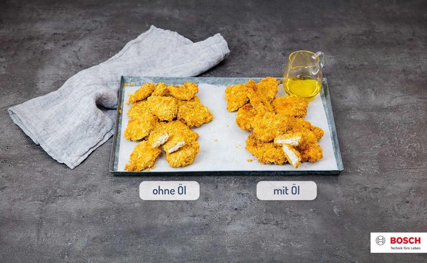 Zwei verschiedene Chicken Nuggets im Vergleich auf einem Backblech liegend.
