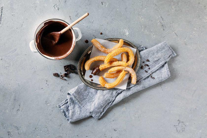 Churros auf Teller mit einer Schale Schokolade.