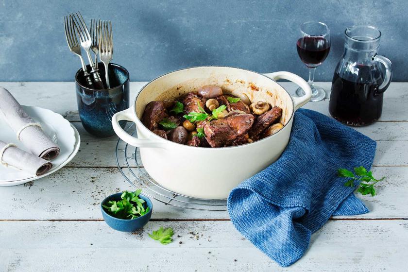Coq au Vin in einem Schmortopf auf einem Tisch mit Tellern angerichtet.