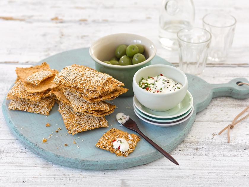 Cracker liegen auf einem Teller mit Oliven und Dip.