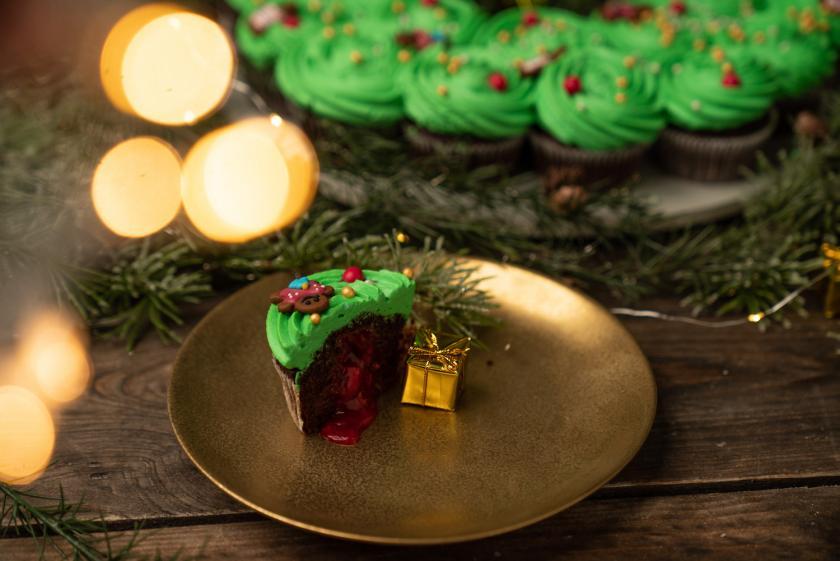 Schokoladen-Cupcakes mit grünem Frosting zu einem Adventskranz drapiert.