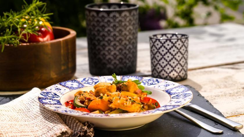Curryreis mit Hähnchen und Gemüse im tiefen Teller auf dem Gartentisch.