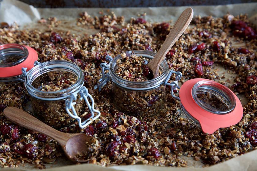 Dinkelmüsli in mehreren Gläsern abgefüllt auf einem Blech mit Dinkelmüsli.