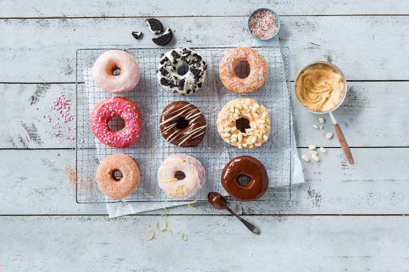 Neun Donuts mit verschiedenen Glasuren auf einem Kuchengitter.