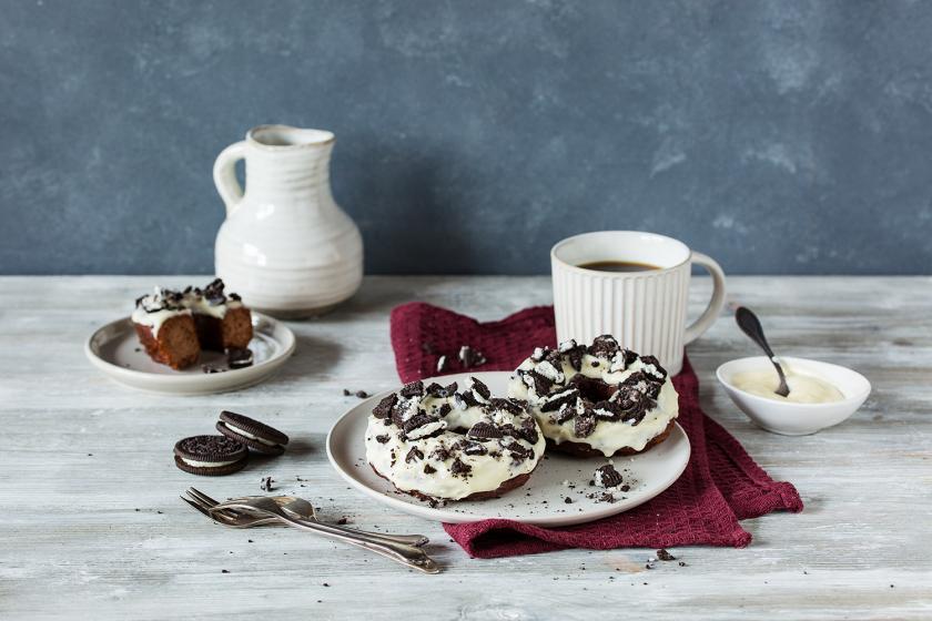 Sei Donuts Oreo liegen auf einem Teller. Drum herum ein gedeckter Kaffeetisch.