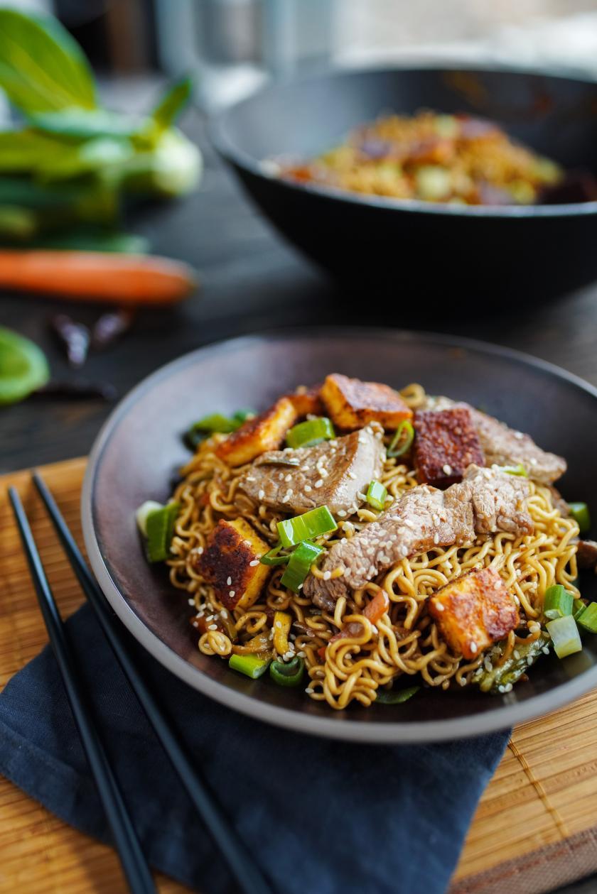 Asiatische Nudelpfanne mit Rinderfiletstreifen und Gemüse in schwarzen Schalen.
