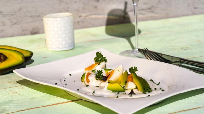Eiersalat ohne Mayo, aber mit Avocadospalten und Joghurtdressing angerichtet auf einem Teller