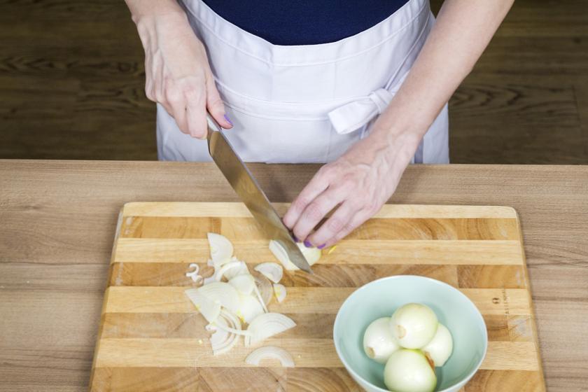 Für den Elsässer Flammkuchen werden Zwiebeln in Streifen geschnitten.