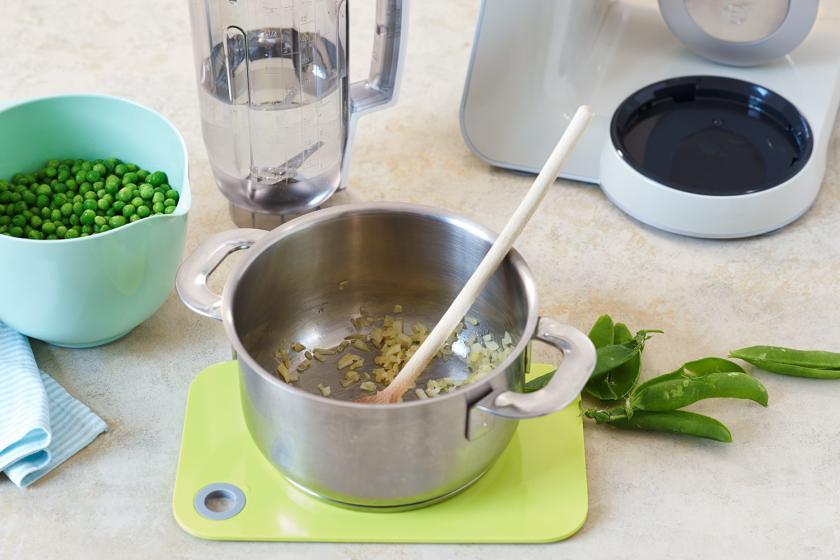 Für Erbsencremesuppe wird eine Zwiebel in einem Topf angebraten.