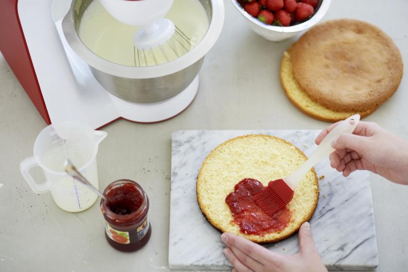 Der Boden für Erdbeer-Sahne-Torte wird mit Marmelade bestrichen.