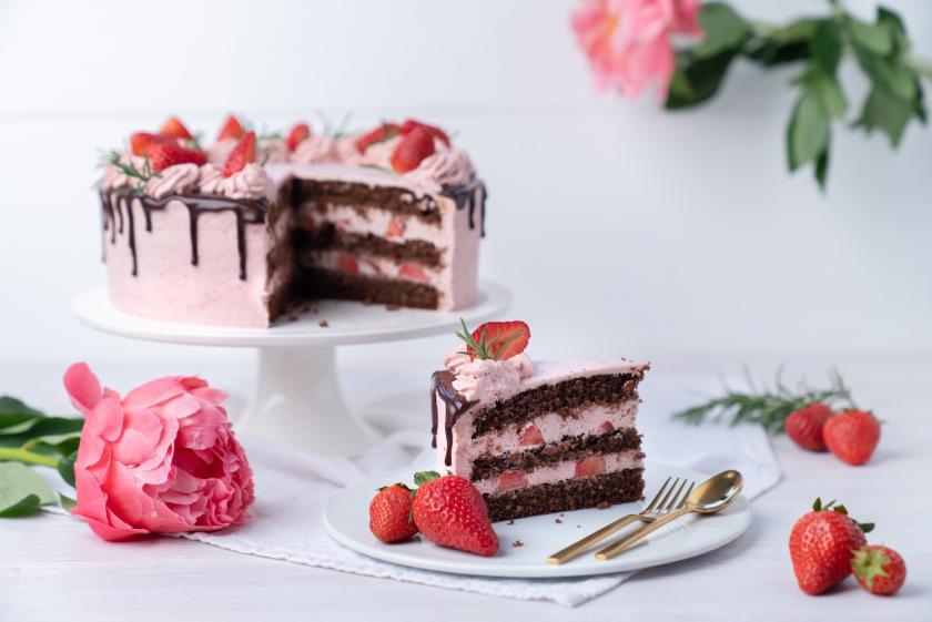 Angeschnittener Erdbeer-Drip-Cake auf Tortenplatte.