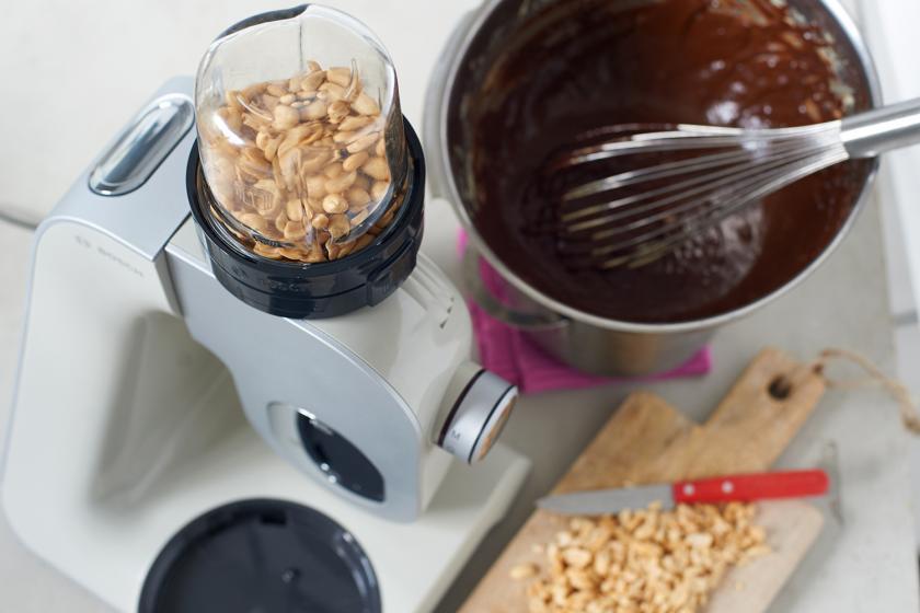 Für die Erdnuss-Brownies werden Nüsse in einer Küchenmaschine gemahlen. Daneben geschmolzene Schokolade.