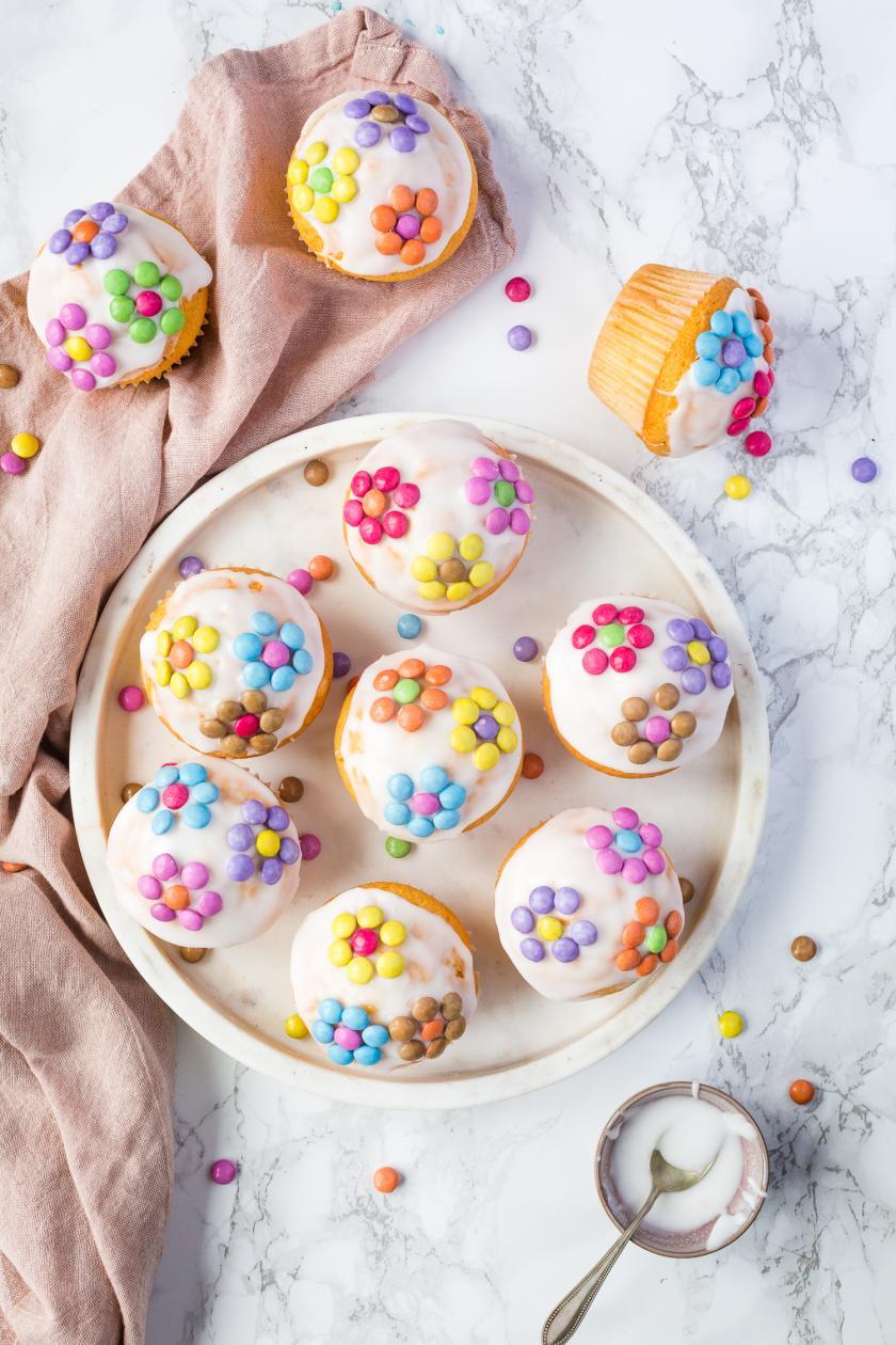 Neun bunte Fanta-Muffins mit Smarties-Blumen von oben fotografiert.