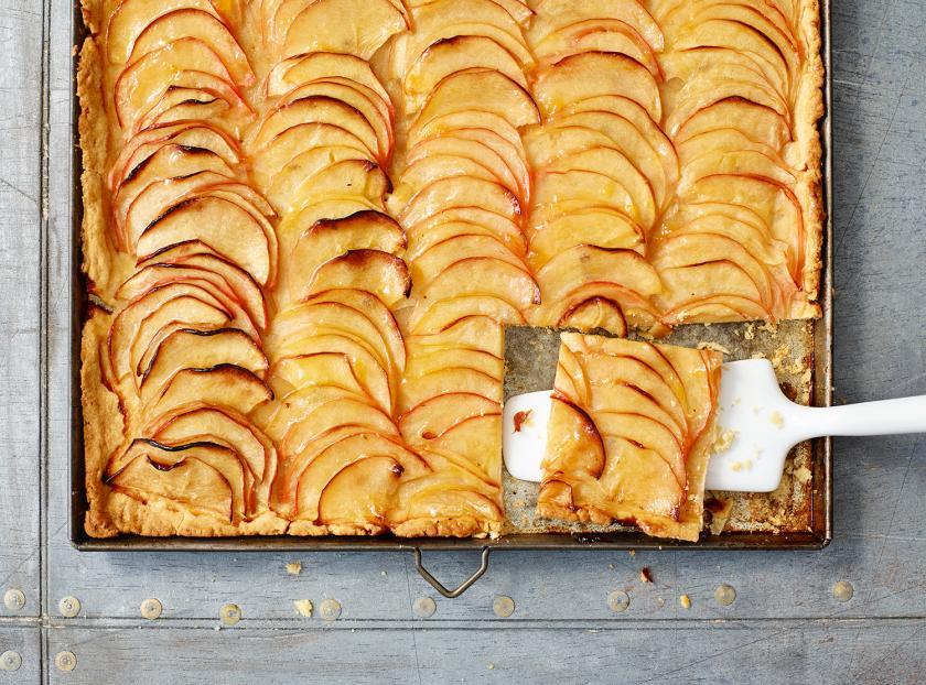 Französischer Apfelkuchen auf einem Backblech angeschnitten.