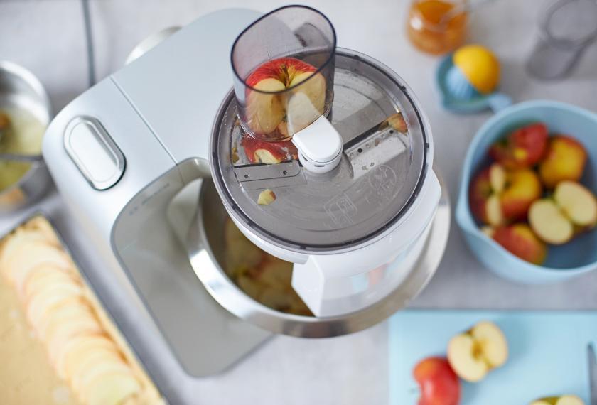 Äpfel für französischer Apfelkuchen werde mit einer Küchenmaschine in feine Scheiben gehobelt.