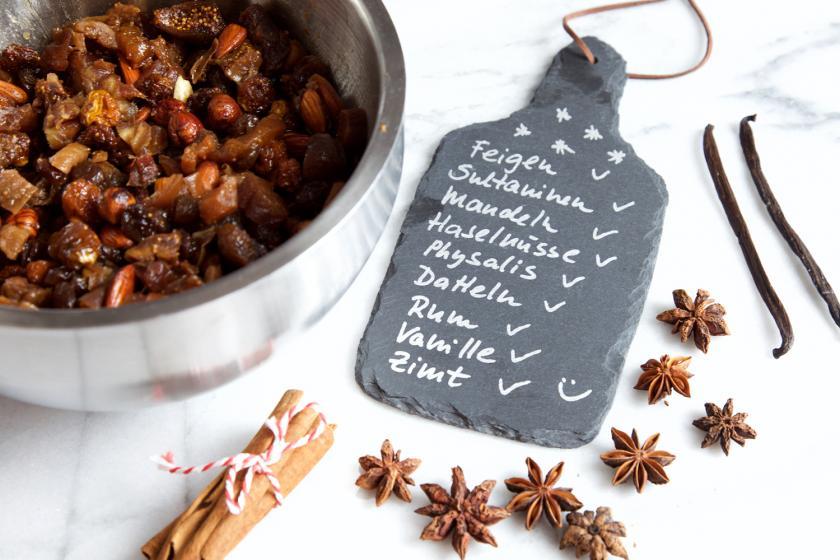 Für den Früchtekuchen werden Sultanien in einer Schüssel mit Rum eingeweicht. Daneben eine Tafel mit den Zutaten aufgelistet.