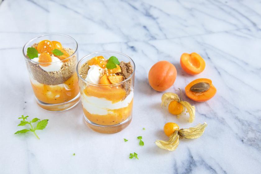 Es ist Frühstück im Glas angerichtet. Zwei Gläschen stehen auf einem Marmoruntergrund, daneben Aprikosen.
