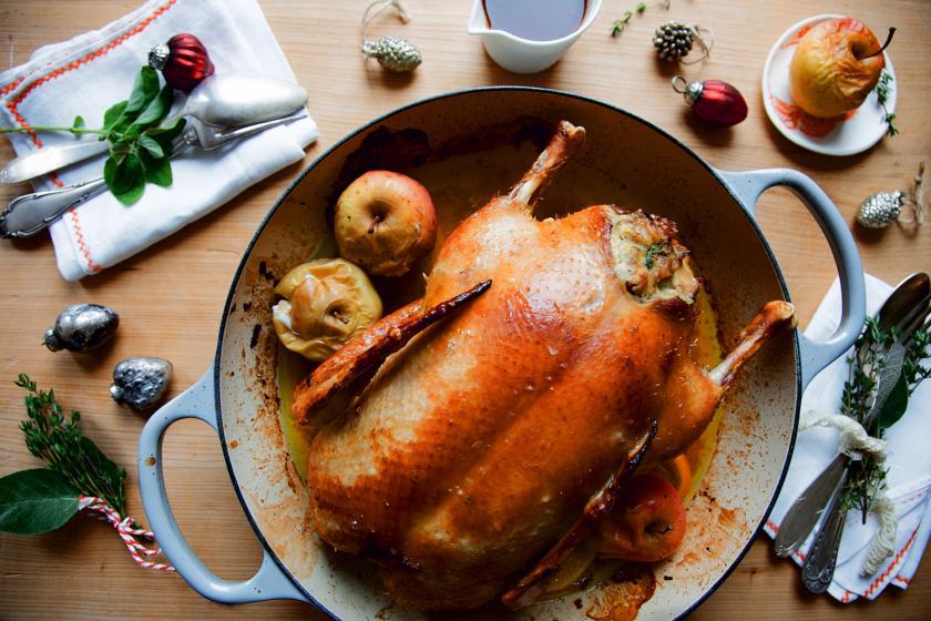 Gefüllte Ente mit Äpfeln in einem Bräter auf einem gedeckten Tisch.