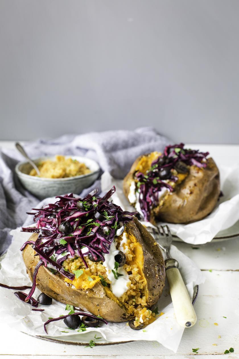 Gefüllte Süßkartoffel mit Bulgur und Rotkohl angerichtet.