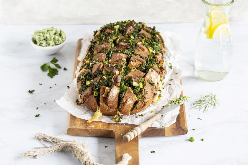 Ein gefülltes Brot ist auf einem Holzbrettchen angerichtet.