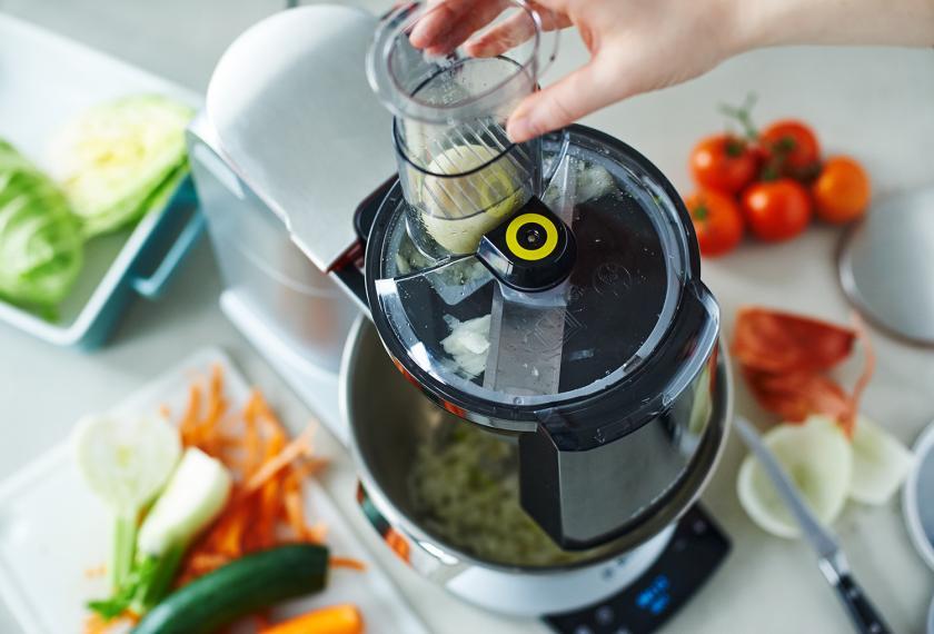 Gemüse für Gemüselasagne vegetarisch wird mit einer Küchenmaschine geschnitten.