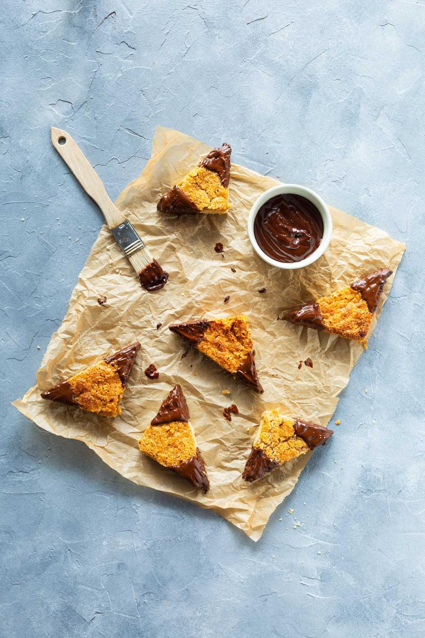Glutenfreie Nussecken mit Schokolade auf einem Stück Backpapier.