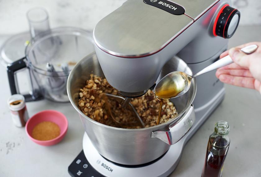 Ahornsirup wird zu Granola mit Nüssen in einer Küchenmaschine gegeben.