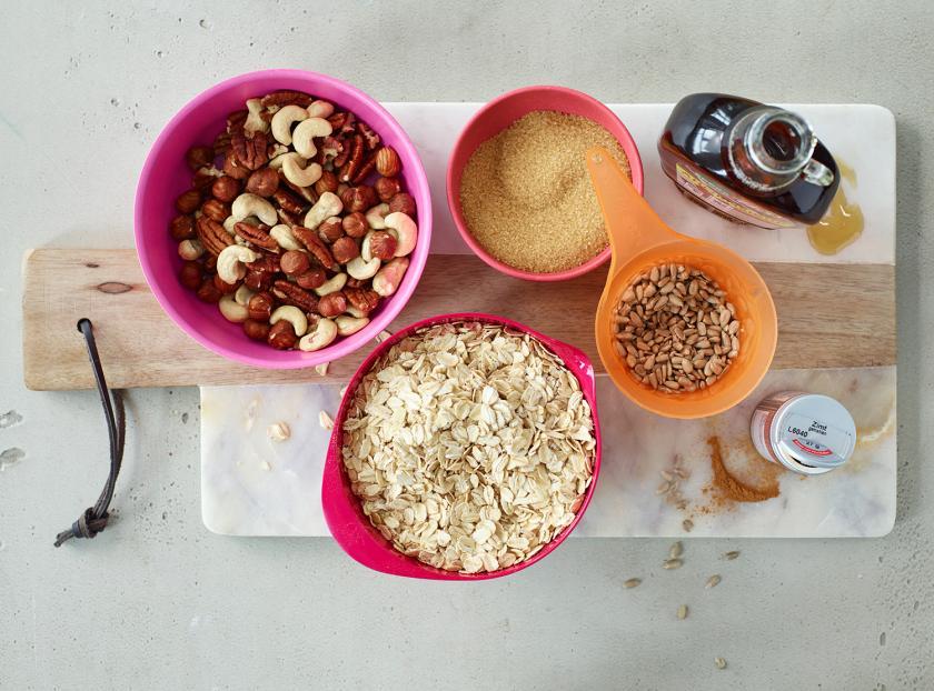 Zutaten für Granola mit Nüssen in kleinen Schalen auf einem Brett.