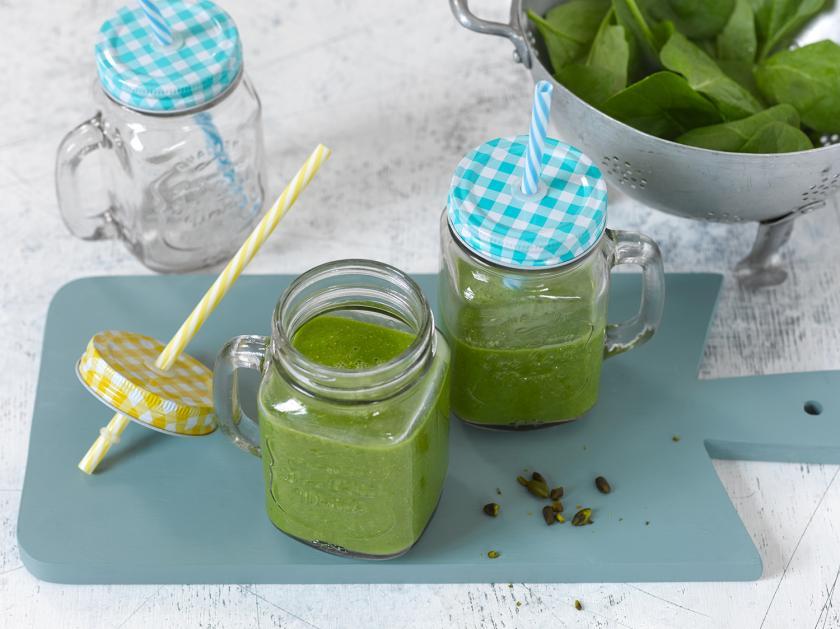 Grüner Smoothie auf zwei Gläser mit Strohhalm ausgeteilt.