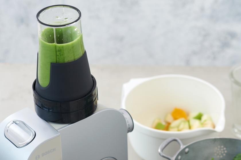 Ein grüner Smoothie wird in einem Mixer püriert.