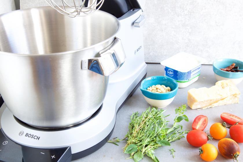Der teig für die Mini-Muffins mit Tomaten wird in einer Küchenmaschine zubereitet. Drumherum Tomaten, Kräuter und Co.