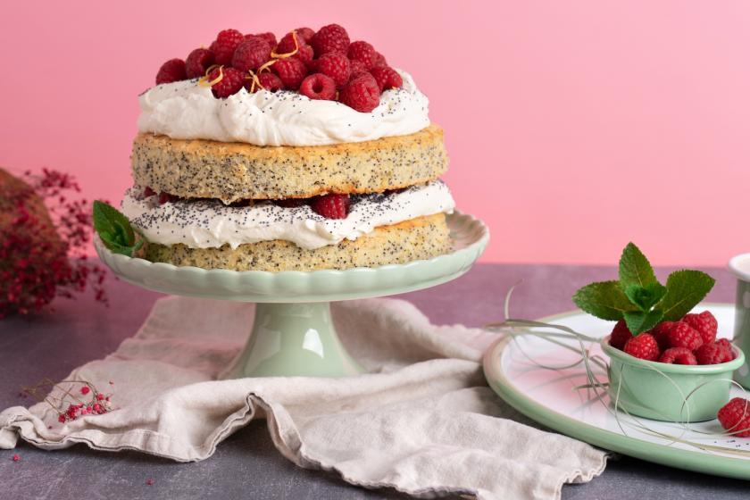 Himbeer-Zitronen-Torte auf Tortenplatte mit Himbeer-Dekoration.