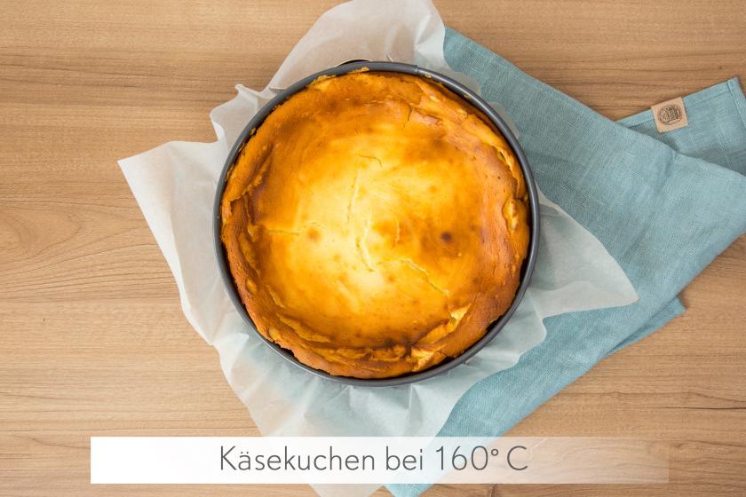 Ganzer Käsekuchen ohne Boden steht mit der Form auf einem blauen Tuch.